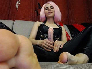 Domme in leather strokes her strap-on
